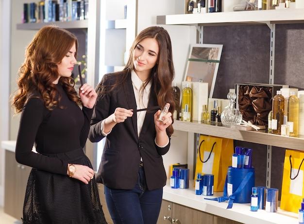 Cliente de sorriso positivo do serviço da vendedora dos jovens na loja de perfume.