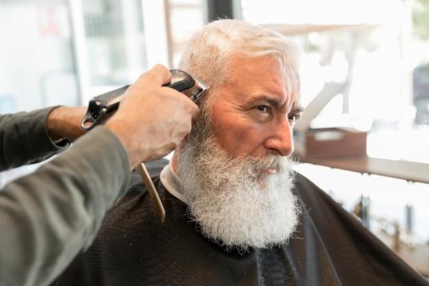 Cliente do aparamento do barbeiro no salão de beleza