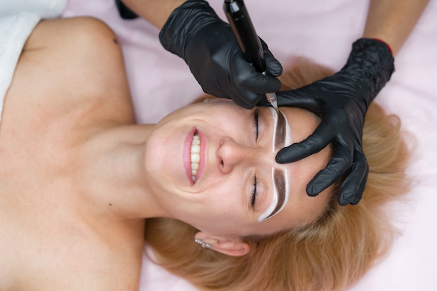 Cliente do gabinete de cosmetologia encontra-se no sofá. esteticista aplica tinta permanente nas sobrancelhas.