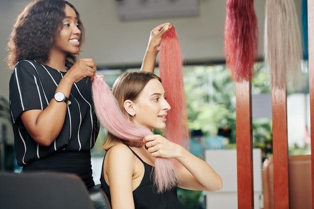 Cliente do salão de beleza escolhendo extensões de cabelo rosa claro