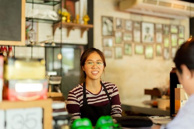 Cliente do serviço do barista da jovem mulher com a cara do sorriso na barra contrária no café.
