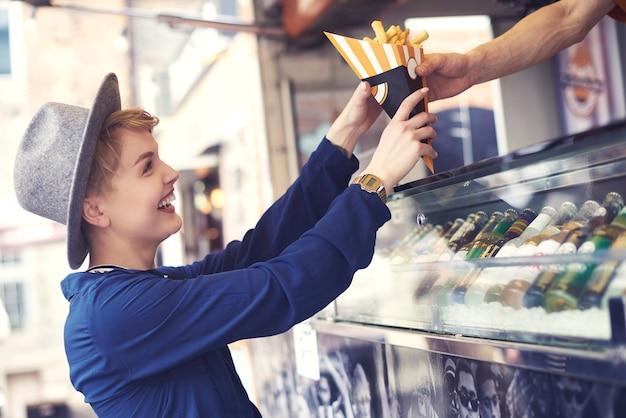 Cliente do sexo feminino alcançando comida do vendedor Foto gratuita