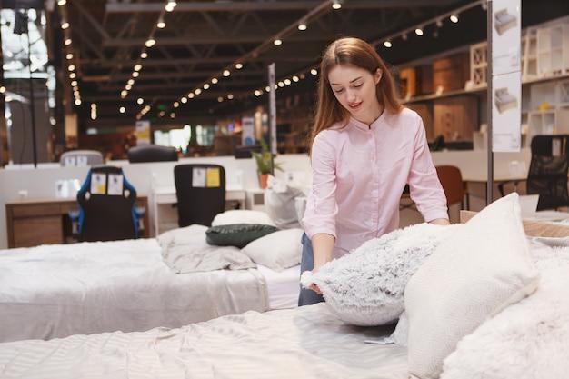Cliente do sexo feminino atraente examinando almofadas à venda em loja de móveis local