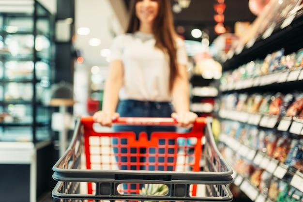 Cliente do sexo feminino com carrinho na loja de alimentos