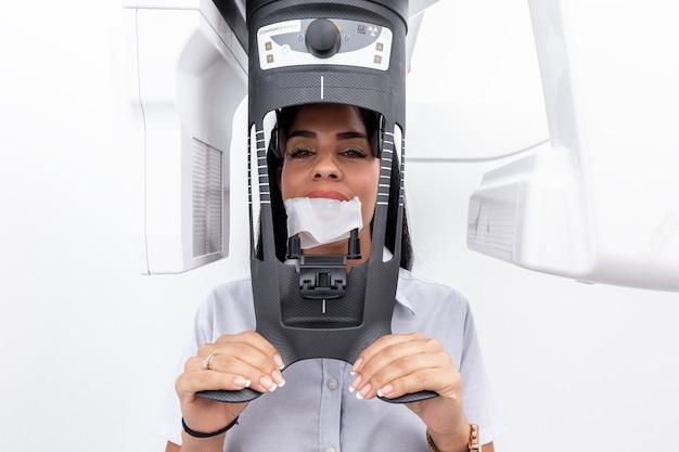 Cliente do sexo feminino com o rosto em uma máquina de clareamento dentário em uma clínica odontológica