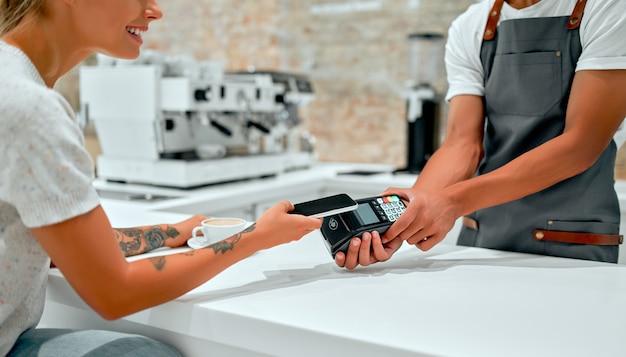Cliente do sexo feminino fazendo pagamento por telefone celular no balcão de um café com o barista segurando um cartão de crédito