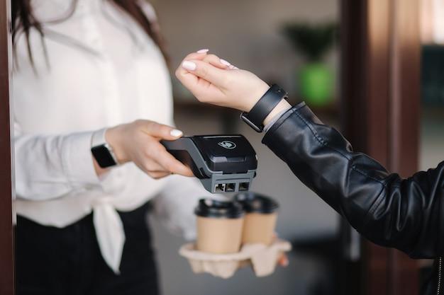 Cliente do sexo feminino fazendo pagamento sem fio ou sem contato usando caixa do smartwatch e aceitando pagamento