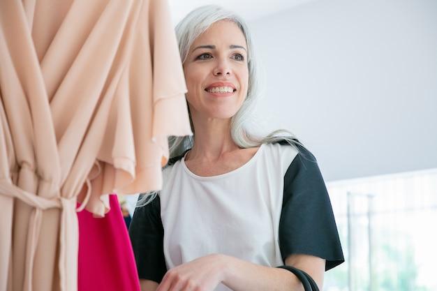 Cliente do sexo feminino feliz desfrutando de compras, em pé perto da prateleira com vestidos. desviando o olhar e sorrindo. mulher comprando roupas em loja de moda. conceito de compras ou varejo