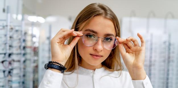 Cliente do sexo feminino feliz ou oculista está de pé com conjunto de óculos