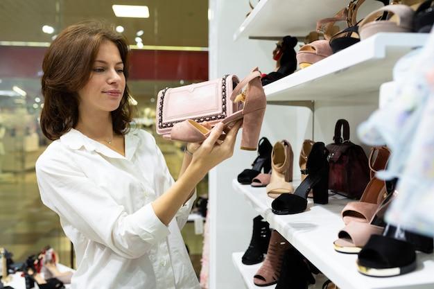 Cliente do sexo feminino jovem segurando bege par de sapatos da moda em uma mão e bolsa rosa em outro, combinando detalhes