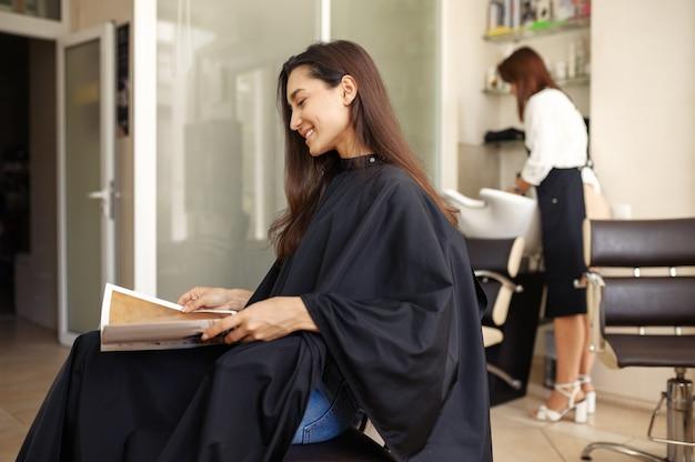 Cliente do sexo feminino no espelho no salão de cabeleireiro. estilista e cliente em hairsalon. negócio de beleza, serviço profissional