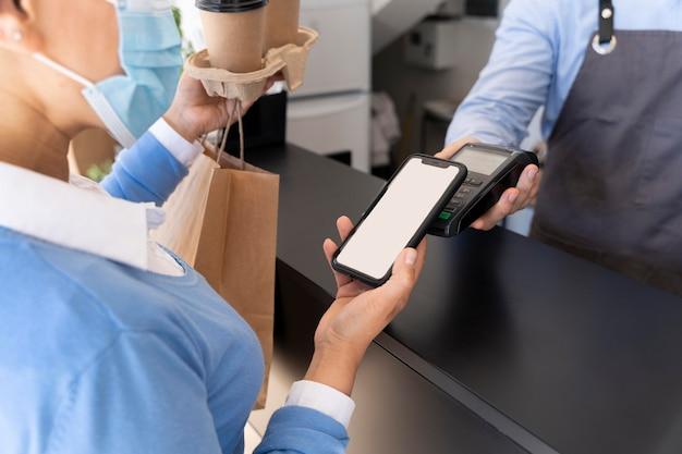 Cliente do sexo feminino pagando comida para viagem com smartphone