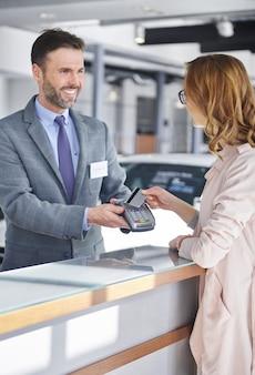 Cliente do sexo feminino pagando por nova compra