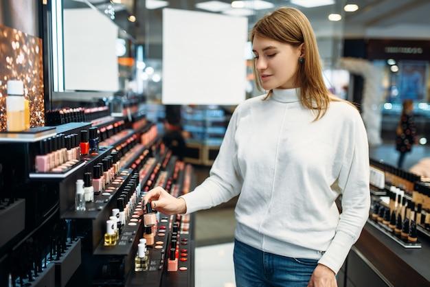 Cliente do sexo feminino procurando cosméticos na loja de maquiagem. escolha de verniz para unhas em loja de beleza, salão de maquiagem