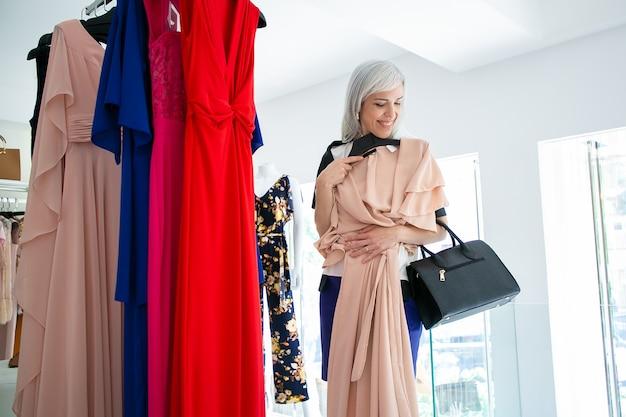Cliente do sexo feminino satisfeita escolhendo o vestido de festa, aplicando o pano com cabide e sorrindo. tiro médio. loja de moda ou conceito de consumismo
