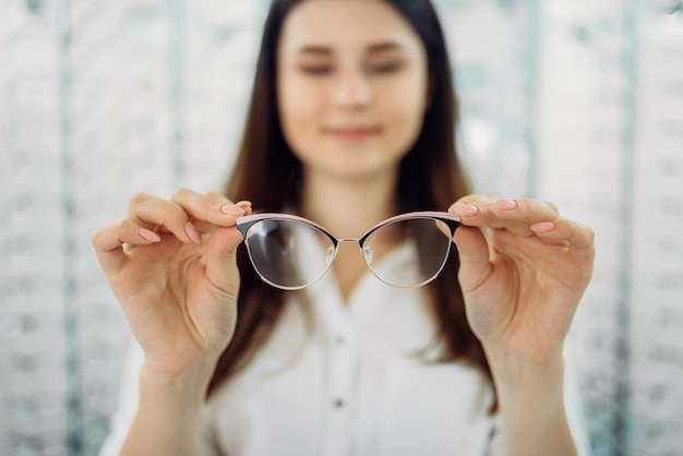 Cliente do sexo feminino segurando óculos, loja de ótica