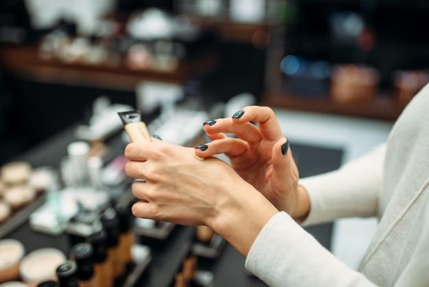 Cliente do sexo feminino testando creme de base na loja de maquiagem. cosméticos escolhendo em loja de beleza, salão de maquiagem