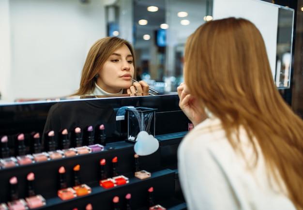 Cliente do sexo feminino testando o delineador labial na loja de maquiagem. cosméticos escolhendo em loja de beleza, salão de maquiagem
