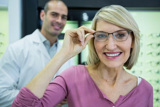 Cliente do sexo feminino usando óculos na loja de óptica