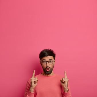 Cliente do sexo masculino chocado assustado, fascinado pelo anúncio da oportunidade, aponta para cima com expressão surpresa, mostra o espaço em branco para o anúncio, demonstra venda incrível, isolado na parede rosa