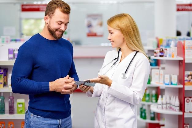 Cliente do sexo masculino conversando discretamente com o farmacêutico na farmácia