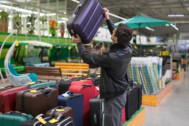 Cliente do sexo masculino, escolhendo a mala de viagem no supermercado. ele pegou a bolsa.