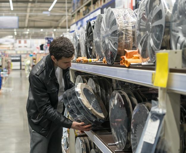 Cliente do sexo masculino escolhendo novas tampas de roda no supermercado. manutenção do carro.