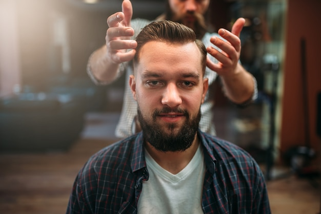 Cliente do sexo masculino feliz após fazer penteado na barbearia