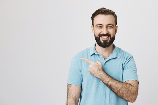 Cliente do sexo masculino satisfeito e feliz, sorrindo e apontando para a esquerda para a copyspace