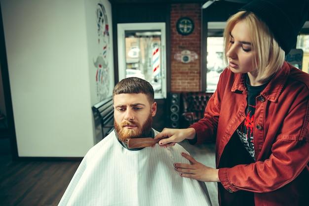 Cliente durante o barbear na barbearia. barbeiro feminino no salão. igualdade de gênero