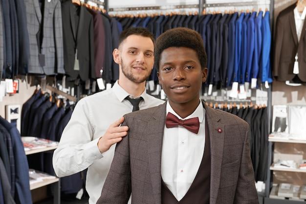 Cliente e assistente posando em roupas elegantes na boutique.