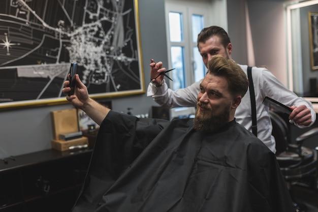 Cliente e barbeiro levando selfie