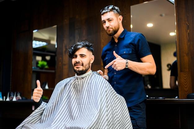Cliente e cabeleireiro olhando para a câmera
