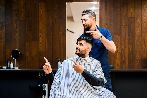 Cliente e cabeleireiro olhando para longe