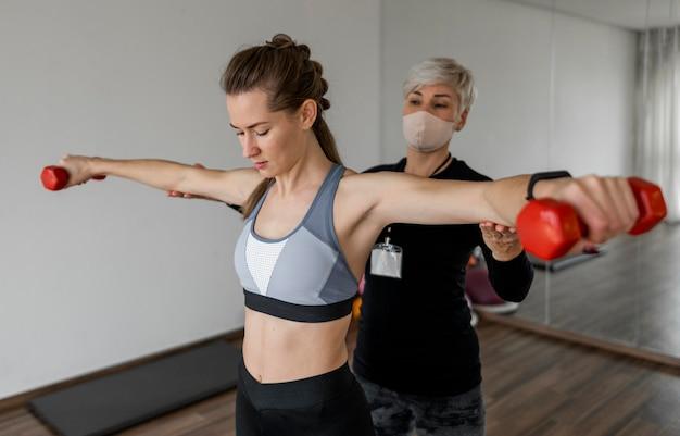 Cliente e personal trainer feminina usando halteres vermelhos