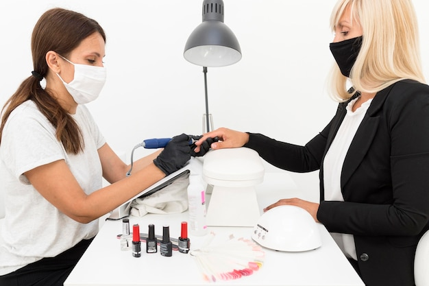 Cliente e trabalhador de vista lateral usando máscaras em salão de beleza