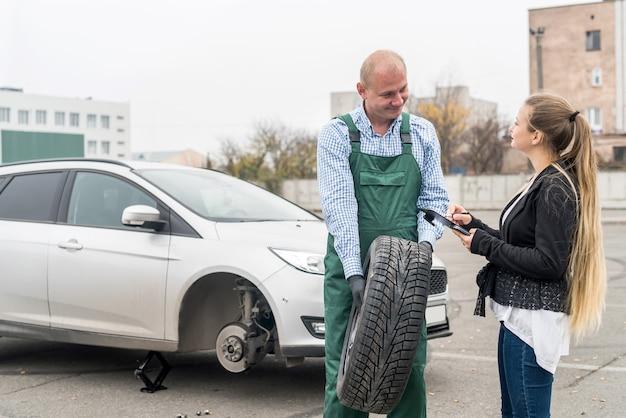 Cliente e trabalhador na estação de serviço com carro