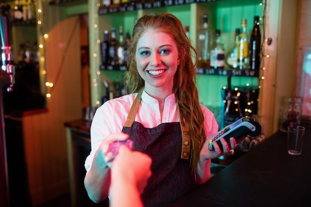 Cliente efetuando pagamento por cartão de crédito no balcão
