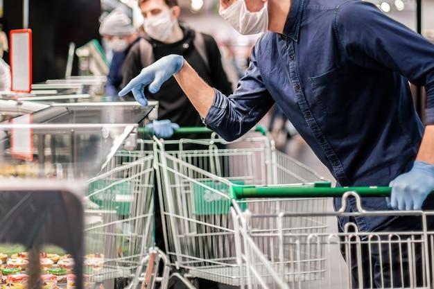 Cliente em luvas de proteção escolhendo produtos em um supermercado. higiene e cuidados de saúde