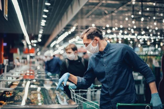 Cliente em luvas de proteção olhando os produtos na geladeira. higiene e cuidados de saúde