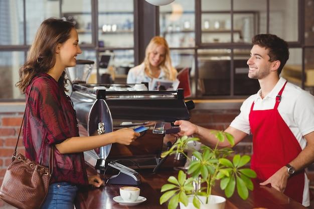 Cliente entregando um cartão de crédito para o garçom