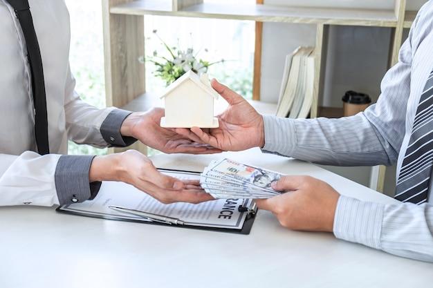 Cliente enviando dinheiro comprando empréstimo residencial e dando as chaves do agente após assinatura do contrato