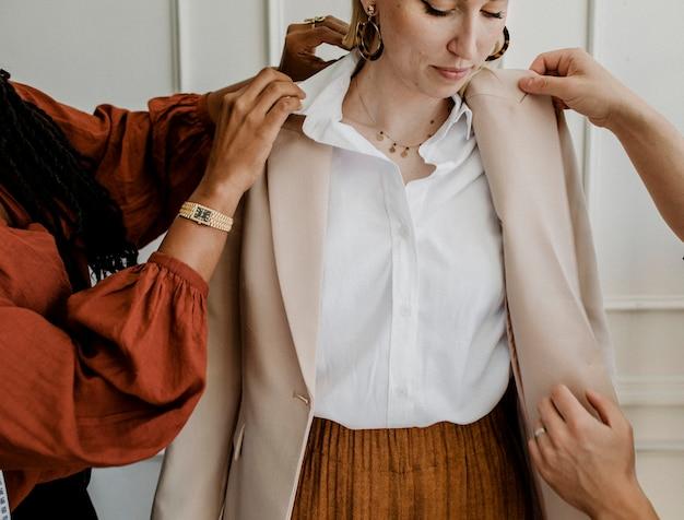 Cliente experimentando um casaco de alta costura