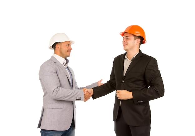 Cliente feliz de meia-idade e engenheiro apertando as mãos isoladas no fundo branco.