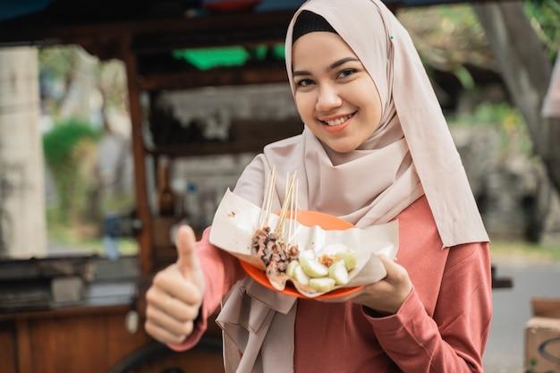 Cliente feliz desfrutando de frango espetado e mostrando o polegar