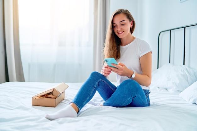 Cliente feliz, jovem e satisfeito por comprar compras, sentado em uma cama em casa com uma caixa de pacote recebida após um pedido on-line, conceito de entrega de comércio de serviço fácil e rápido