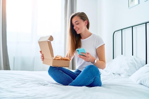 Cliente feliz, jovem e satisfeito por comprar compras, sentado em uma cama em casa e abrindo a caixa de pacote recebida após o pedido on-line, conceito de entrega de comércio de serviço fácil e rápido