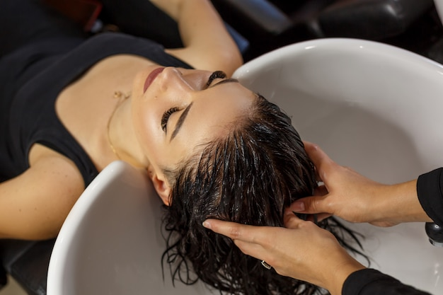 Cliente feliz no cabelo limpo dos cuidados capilares do salão de beleza.