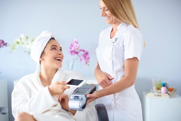 Cliente feliz pagando por tratamentos de spa