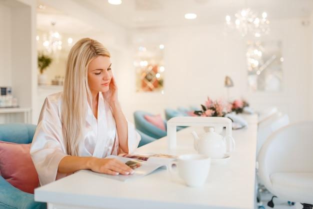 Cliente feminino bebe café no salão de beleza.